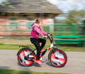 Small girl in motion riding down the street intentional blur Royalty Free Stock Photos