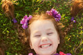 Small girl with pigtails lying on grass green and smiling summer holidays Royalty Free Stock Photos