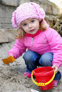 The small girl in pink clothes plays sand Royalty Free Stock Photos