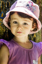 Small girl in pink hat leaning against a wall Royalty Free Stock Image