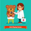 Small girl playing a doctor with teddy bear toy Royalty Free Stock Photo