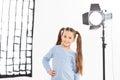 Small girl smiles charmingly during shooting