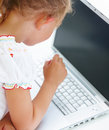 Small girl thinking by laptop Royalty Free Stock Photos
