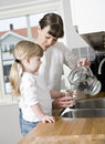 Small girl with water in the kitchen her mother drinking Stock Image