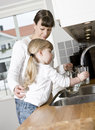 Small girl with water in the kitchen her mother drinking Royalty Free Stock Images