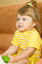 Small girl in yellow eat green apple Stock Photo