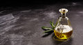 Small Glass Bottle of Olive Oil on Dark Surface Royalty Free Stock Photo