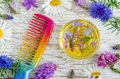 Small glass bowl with aroma cosmetic oil with flowers extracts and hair comb. Ingredients of natural cosmetic. Royalty Free Stock Photo