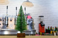 Small green Christmas tree in wooden support over restaurant tab Royalty Free Stock Photo
