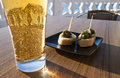 Small green peppers bites with beer padron bread in a plate a glass of in a table of a terrace near the sea Stock Photos