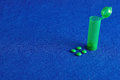 Small green pills with a little green pill bottle Royalty Free Stock Photo