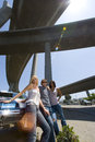 Small group of friends by car beneath overpass portrait low angle view lens flare Stock Photo