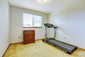 Small gym room bright with one window and carpet floor running exercise equipment and wooden cabinet Royalty Free Stock Photos