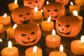 Small halloween toy pumpkins surrounded by orange tealight candles Royalty Free Stock Image
