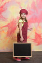 Small happy girl chef in hat, apron with blackboard Royalty Free Stock Photo