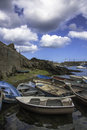 Small harbour rowing boats tied in a group inside cornish with blue sky and heavy clouds Stock Photography