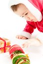 Small hild dressed as santa claus сhild pulls a hand to the present Stock Photos