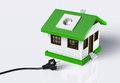 Small house disconnected to the electric current a with a socket on roof is from a black cabled plug that lies on ground on a Royalty Free Stock Image