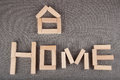 Small house figure and word home made of toy wooden bricks lay on grey background Royalty Free Stock Photo