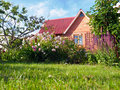 Small house in a flower garden Royalty Free Stock Photos