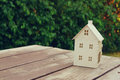 Small house model over wooden table outdoors at garden selective focus . filtered image Royalty Free Stock Photo