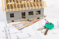 Small house under construction, keys and currencies euro on electrical drawings for project, building home cost concept Royalty Free Stock Photo