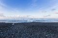 Small ice on black rock sand beach seacoast skyline Royalty Free Stock Photo