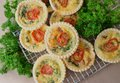 Small individual quiche with parsley each topped a slice of tomato stacked on a wire cooling rack Stock Photography