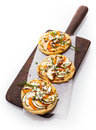 Small individual vegetarian italian pizzas three served on a long wooden board topped with eggplant cheese herbs chives and bell Stock Image