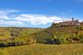 Small italian town on the hill with vineyards typical over autumnal under beautiful sky in piedmont northern italy Royalty Free Stock Images