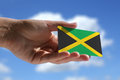 Small jamaican flag against sky with cumulus clouds Stock Image