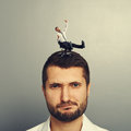 Small joyful man rolling on the head big dissatisfied Stock Photo