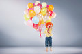 Small jumping boy holding bunch of balloons Royalty Free Stock Photo