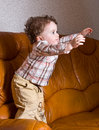 Small kid with curly hair on a leather brown sofa Royalty Free Stock Image