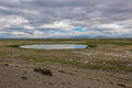 A small lake in the steppe against the backdrop of the mountains sky and clouds reflects sky and clouds Royalty Free Stock Photography