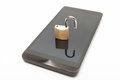 Small lock in unlocked position over smartphone. Mobile phone security and data protection concept Royalty Free Stock Photo
