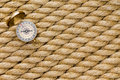 Small magnetic compass on diagonal strands of rope a new natural fiber conceptual nautical navigation and shipping or Stock Photo
