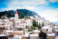 Small mediterranean town on slopes of hill with church on top the a covered in snow Royalty Free Stock Photos
