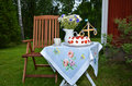 Small midsummer table with coffee cup flowers and strawberry cake ready for celebration outdoors Stock Photo