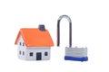 Small model house alongside a padlock Royalty Free Stock Photo