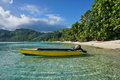Small motor boat moored on sandy shore huahine with tropical vegetation avea bay iti island pacific ocean french polynesia Royalty Free Stock Image