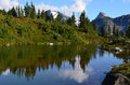 Small mountain lake near m gurr lake bella coola bc canada with reflection of forest and clouds in it Stock Image