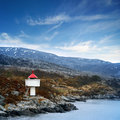 Small norwegian lighthouse under blue sky white tower with red top stands on coastal rocks Royalty Free Stock Photography