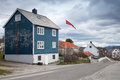 Small norwegian village landscape with colorful wooden houses and flag Royalty Free Stock Image