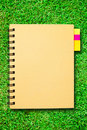 Small notebook on green grass field Stock Photos