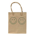 Small and old paper bag with green smile face isolated on white background Stock Image
