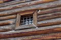 Small old window barred in the log wall Royalty Free Stock Photos