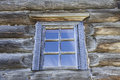 Small Old window with glass with a blue sky on the background of the wooden wall of the countryside log house Royalty Free Stock Photo