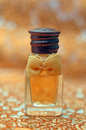 Small perfume bottle with yellow ribbon Stock Photos