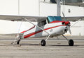Small plane parked a white and red at ramp Stock Images
